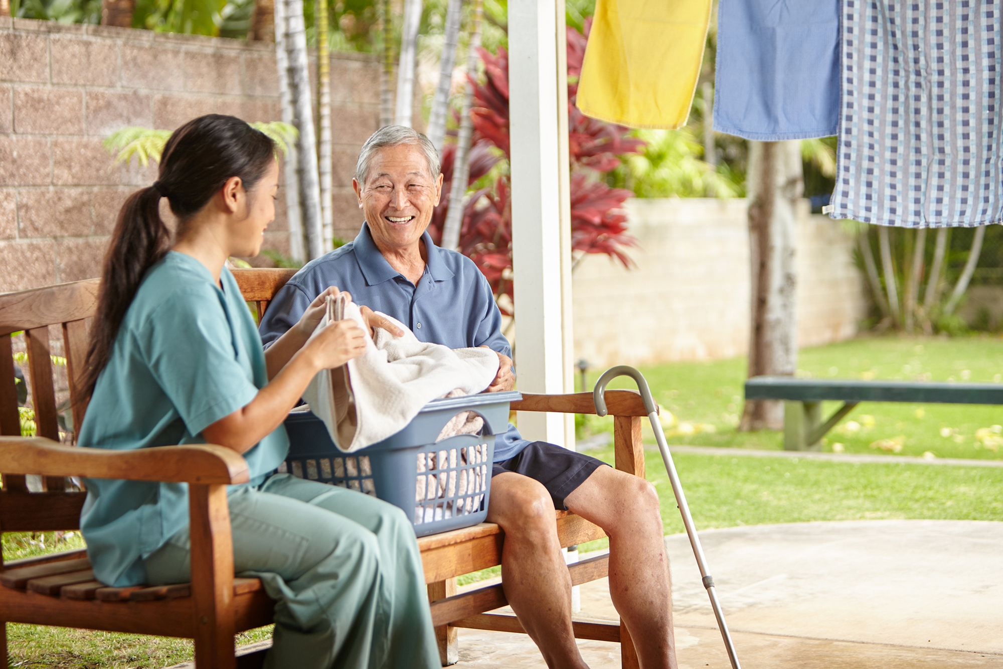 Hawaii senior aging in place with help of home caregiver doing laundry